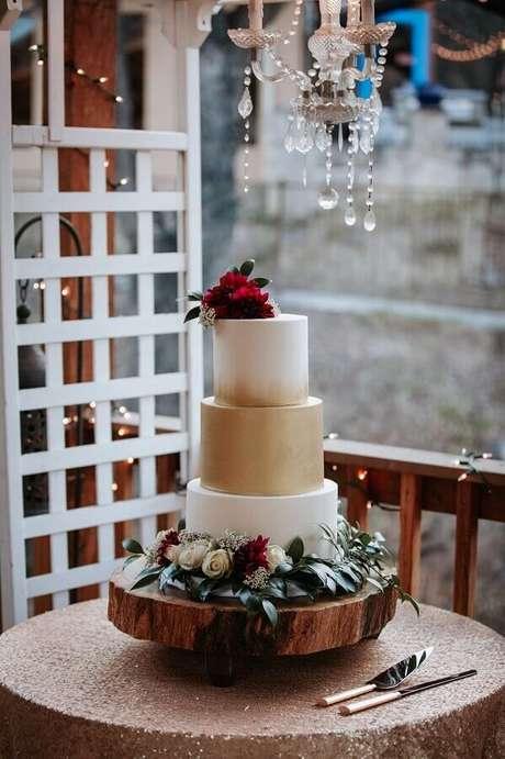 17. Lindo bolo de aniversário de casamento branco e dourado decorado com flores brancas e vermelhas – Foto: Assetproject