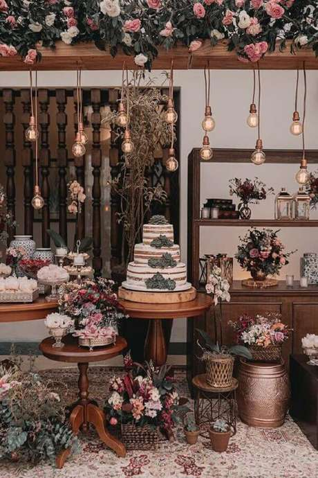 41. Decoração rústica para festa de aniversário de casamento com luminárias e arranjo de flores – Foto: iCasei