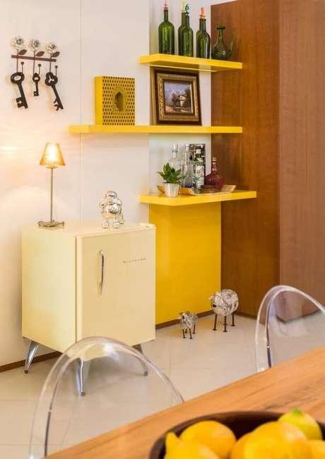 40. Sala de estar com frigobar retrô e prateleiras amarelas combinando – Projeto: Silvana Hilbe