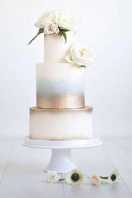 54. Lindo bolo de aniversário de casamento 3 andares com rosas brancas e detalhe metalizado – Foto: ELLE Decoration