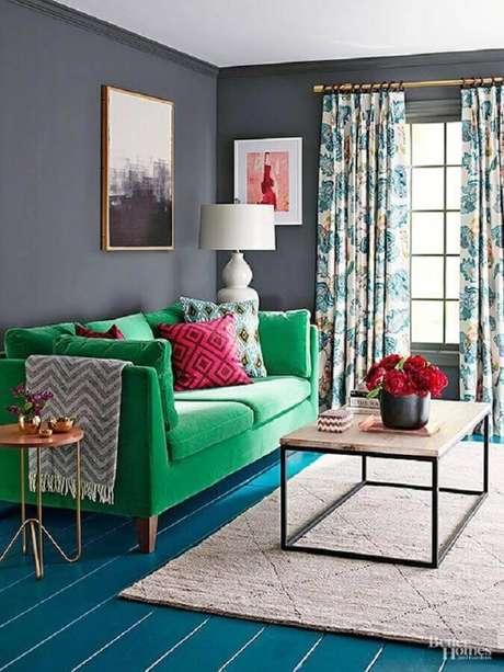 26. Sofá verde para sala com parede cinza e piso azul, móveis retrô bem coloridos e diferentes, não acha?! – Foto: Better Home and Gardens