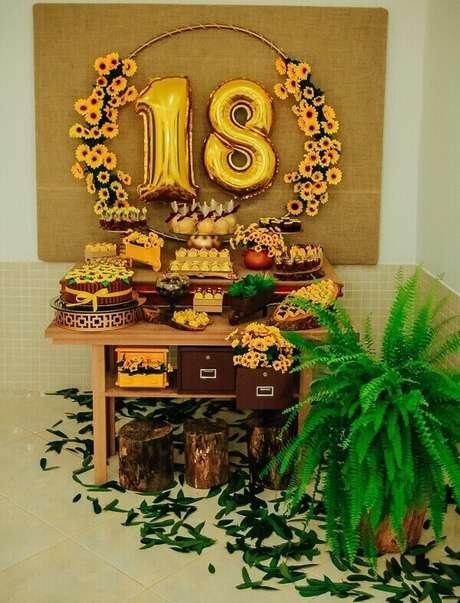 21. Mesa simples para festa tema girassol com mesa de madeira e flor de samambaia. Fonte: Pinterest