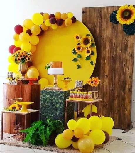 41. Decoração de festa tema girassol com painel de madeira, samambaia e bexigas. Fonte: Pinterest