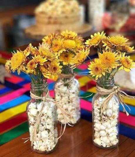 50. Garrafas de vidro transparente e pipoca decoram a mesa dos convidados da festa tema girassol. Fonte: Casa e Festa