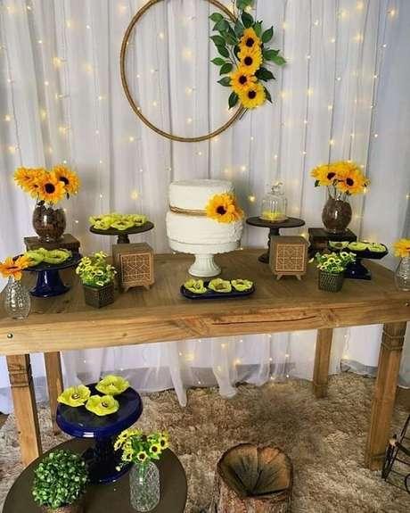 65. Decoração simples para festa tema girassol com cortina de pisca pisca e mesa de madeira. Fonte: Pinterest