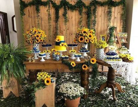 69. Decoração rústica para festa tema girassol com arranjos florais e painel de madeira. Fonte: Pinterest