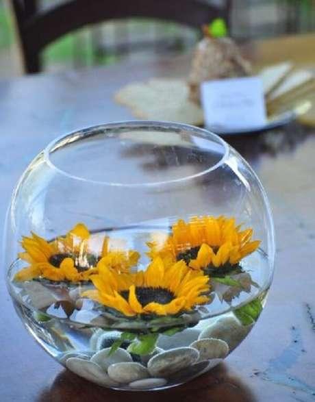 71. Utilize o vaso transparente com pedras, água e flores de girassol para decorar a mesa. Fonte: Pinterest