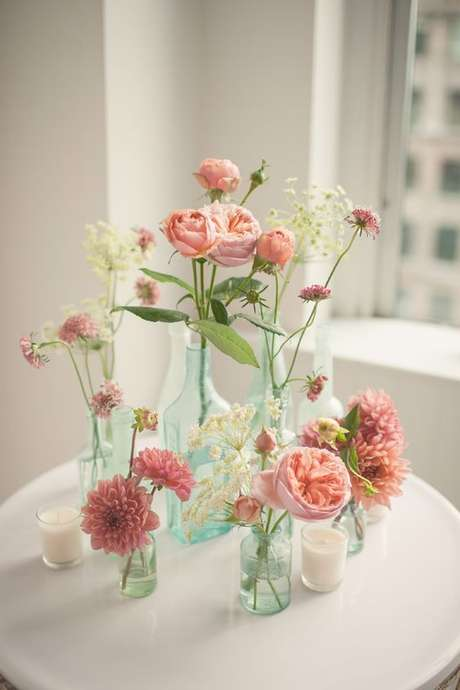 75. Garrafas coloridas com flores cor de rosa – Via: Decor Fácil