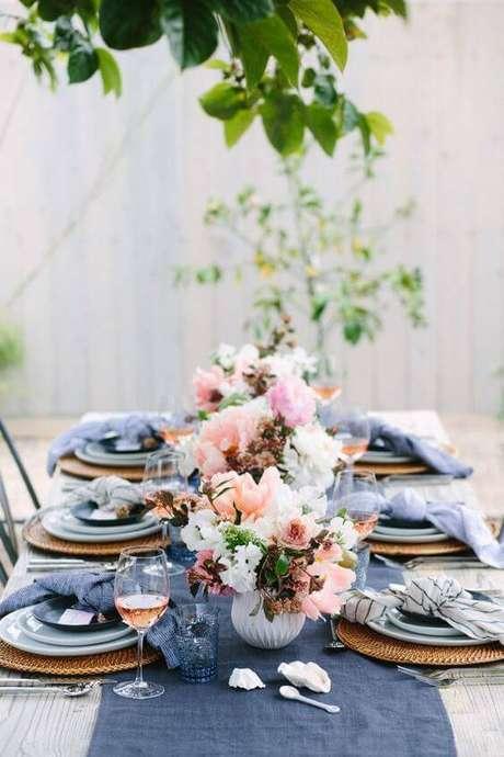 8. A mesa em área externa tem enfeites de flores e em tons de azul.