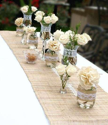 11. O enfeite de mesa pode ter um caminho de tecido rústico para apoiar vasos e potes.