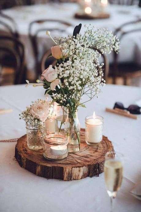 14. Enfeites de mesa com troncos rústicos combinam com flores mosquitinho e potes delicados.