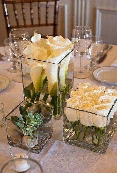 15. Vasos quadrados com flores e suculenta são enfeites de mesa modernos.