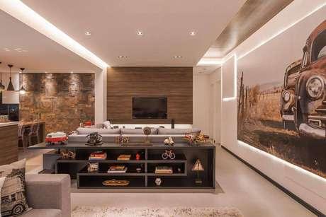 19. A mesa de apoio atrás do sofá tem enfeites com livros e elementos descolados. Projeto por Raduan Arquitetura.