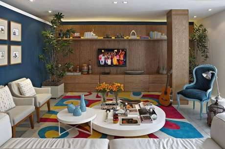 22. A sala de estar com tapete colorido tem enfeites de mesa mais discretos, mas cheios de estilo. Projeto por Gabriel Magalhães e Luiz Claudio Souza Arquitetos.