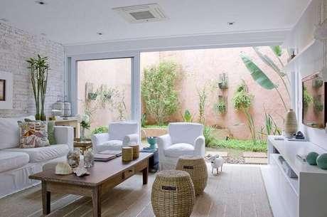 23. A mesa de centro da sala de estar clara conta com elementos estilosos para enfeitar. Projeto por Marilia Veiga.