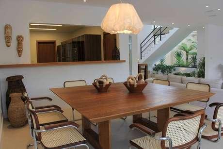 32. A sala de jantar em madeira e palha tem enfeites de mesa discretos e combinando. Projeto por Marcela Stecca Wandenkolk.
