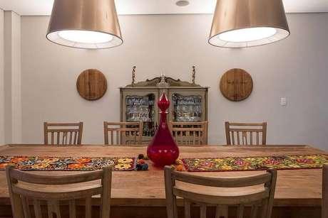 34. O vaso colorido combinado com tapeçarias é um enfeite de mesa vintage. Projeto por Barbara Dundes.