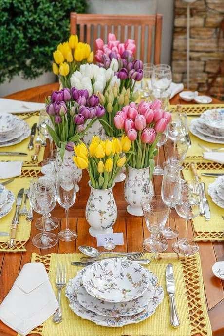 42. Usar múltiplos vasos como enfeites de mesa e flores coloridas traz charme para a área externa.