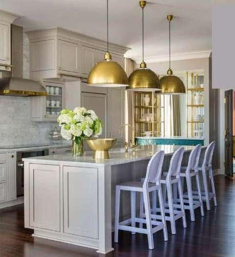 24. O tom dourado da luminária para cozinha pode dar um toque de sofisticação ao ambiente