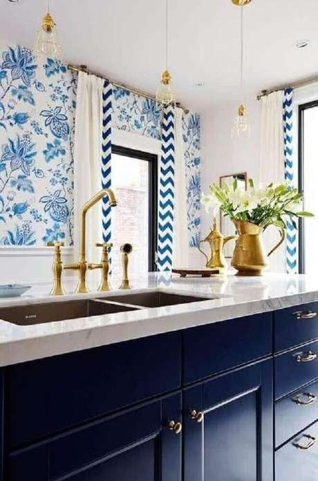 40. A cozinha em tons de azul e dourado recebeu luminária para cozinha com armação e cabos