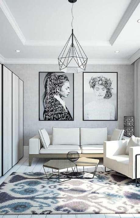 67. Sofá branco, quadros grandes para sala e tapete estampado trazem charme para o ambiente. Fonte: Pinterest