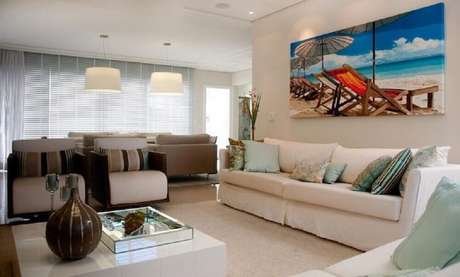56. Sala toda decorada em tons claros com quadro decorativo grande e colorido