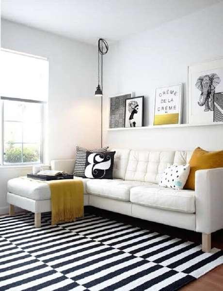 28. Decoração minimalista para sala clean com sofá com chaise branco e prateleira com quadros apoiados – Foto: Archilovers