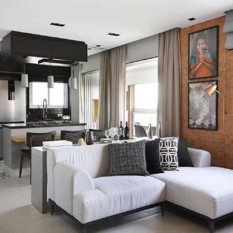 30. Decoração para sala com parede de tijolinho e sofá pequeno com chaise branco – Foto: Juliana Pires Interiores