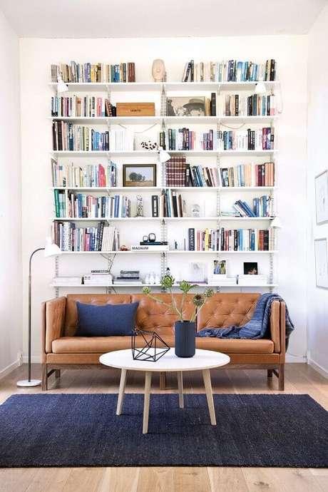 35. Decoração simples para sala com estante de livros e sofá marrom – Foto: Architonic