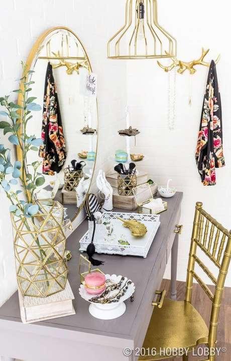 20. Penteadeira com espelho dourado, combinando com a cadeira e lustre da decoração – Via:Hobby Lobby