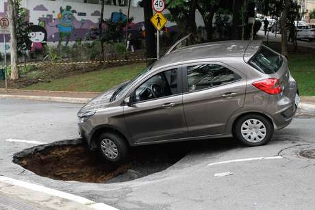 Um veículo caiu no buraco que se abriu após o asfalto ceder na Rua Carlos Comenale, no bairro da Bela Vista.