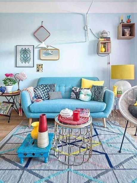 44. Decoração para sala colorida com sofá retrô azul com pés de madeira – Foto: CoachDecor