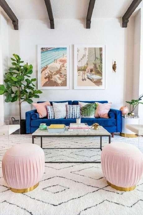 47. Sala de estar clean decorada com sofá de veludo azul e puffs redondos cor de rosa – Foto: Joss & Main