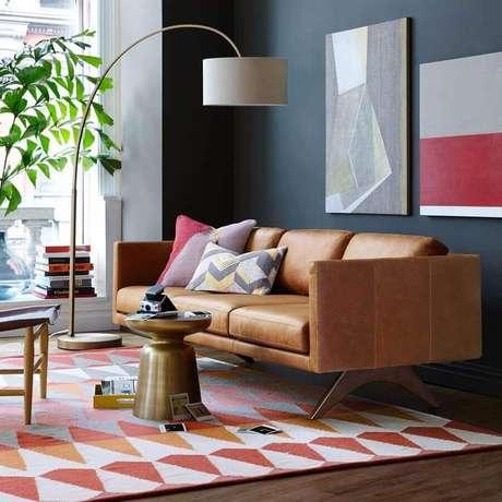 51. Modelo de sofá de couro com design moderno para sala com parede preta e tapete colorido – Foto: Assetproject