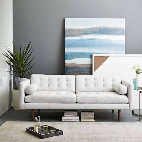 56. Sala moderna decorada com quadros grandes e sofá branco com pés de madeira – Foto: Why Santa Claus