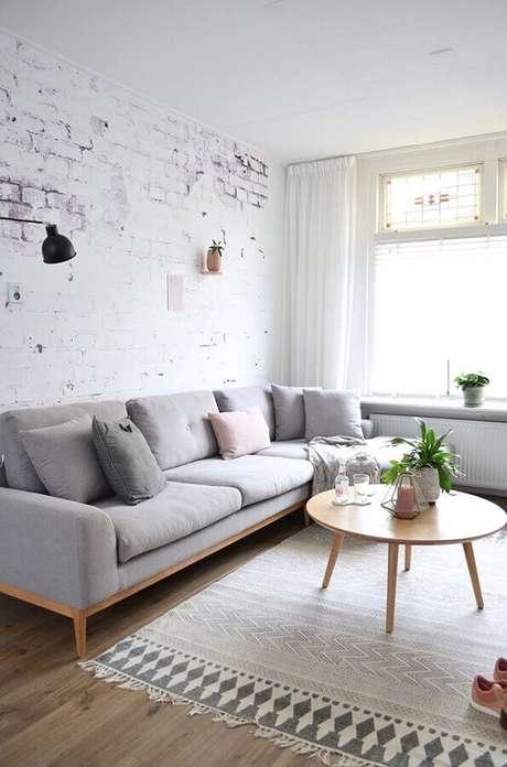 71. Sofá cinza moderno para decoração de sala de estar com parede de tijolinho e mesa de centro redonda de madeira – Foto; Wood Save