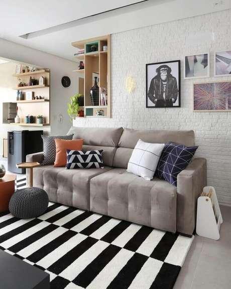 72. Sofá retrátil cinza para decoração de sala de estar com tapete preto e branco listrado e parede de tijolinho branca – Foto: Bianchi & Lima Arquitetura