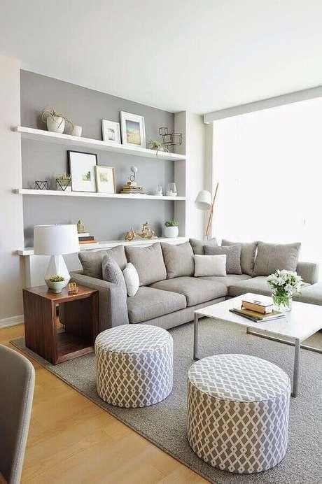 74. Sofá de canto para sala cinza decorada com prateleiras brancas e puffs redondos – Foto: Infinity Design