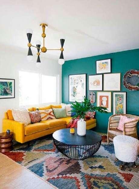 77. Sala colorida decorada com sofá com chaise amarelo e parede verde com vários quadros – Foto: Archilovers