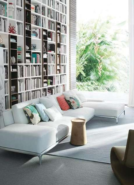 79. Sofá com chaise branco para decoração de sala ampla com parede planejada com estante para livros – Foto: Pinterest
