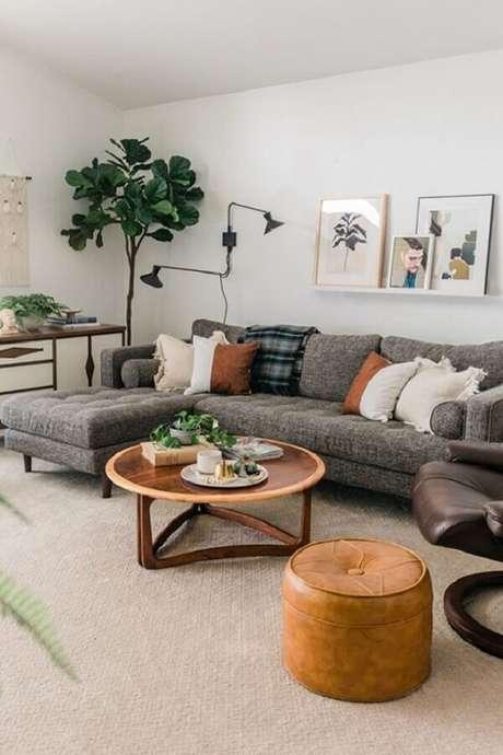 80. Sofá com chaise cinza para sala decorada com puff de couro e mesa de centro redonda de madeira – Foto: Article