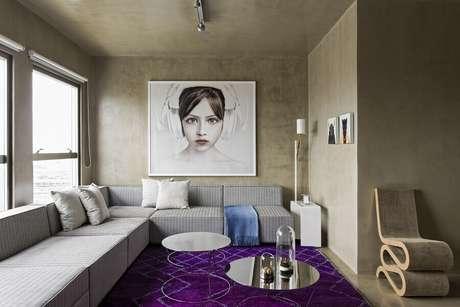 10. Decoração contemporânea para sala com sofá grande e parede de cimento queimado – Foto: Archello