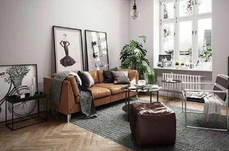 86. Sofá de couro marrom para decoração de sala cinza com quadros grandes – Foto: Behance