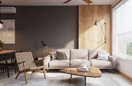91. Sofá moderno para sala decorada com parede cinza e móveis de madeira – Foto: HomeIt