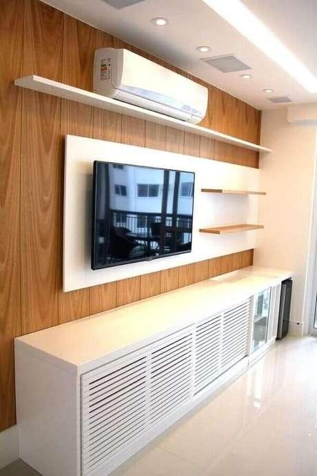 18. Modelos de rack com painel branco e parede revestida com madeira – Foto: BL Arquitetura