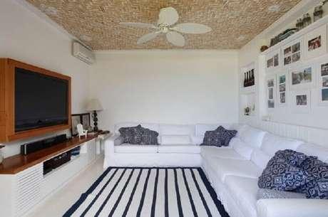 23. Modelos de rack com painel para sala toda branca decorada com tapete listrado azul e branco – Foto: Paola Ribeiro