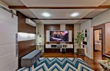 26. Rack com painel branco para decoração de sala ampla com tapete geométrico – Foto: Espaço do Traço Arquitetura