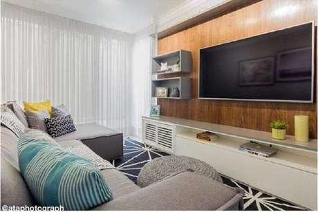 53. Racks modernos com painel de madeira e nicho para decoração de sala com sofá cinza e puff de crochê redondo – Foto: Duda Senna