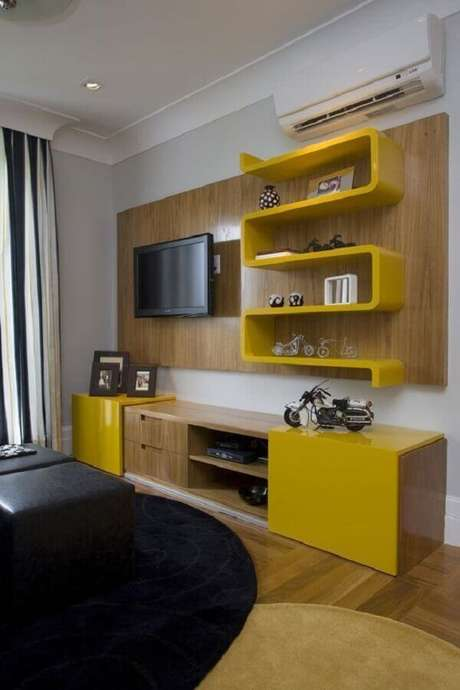 57. Sala simples decorada com rack com painel e nichos amarelos – Foto: HomeIt
