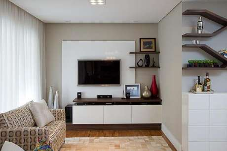 63. Sala simples decorada com rack com painel branco – Foto: Sartori Design